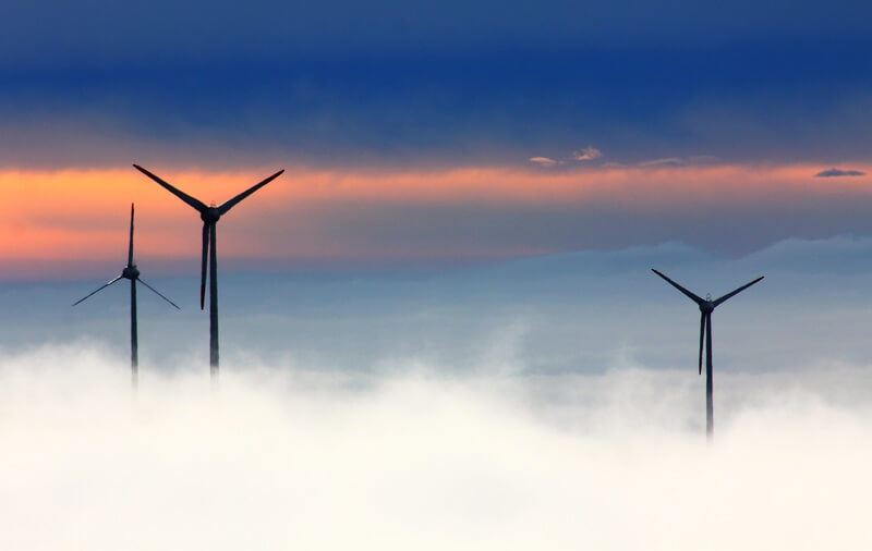 Wind turbines emerging from fog